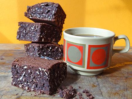stack of home-made coconut brownies with mug of coffee | via @hisforhome #recipe #chocolate #brownies